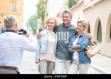 Rear view of man photographing friends in city - Stock Photo