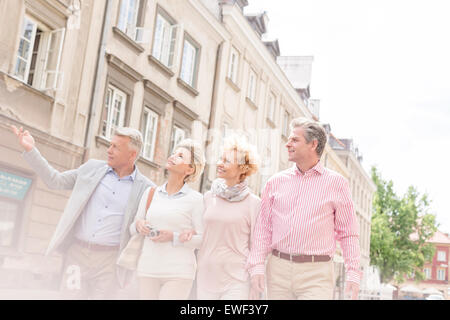Middle-aged man showing something to friends while walking in city - Stock Photo