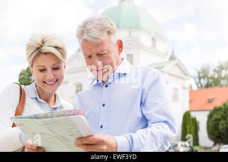 Smiling middle-aged couple reading map outdoors - Stock Photo