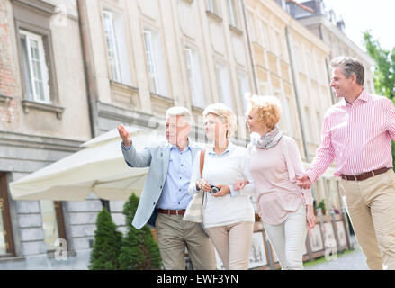 Man showing something to friends while walking in city - Stock Photo