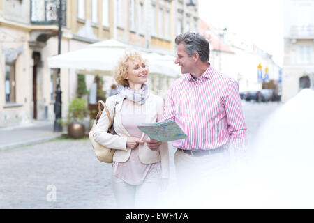 Smiling middle-aged couple with map looking at each other while walking in city - Stock Photo
