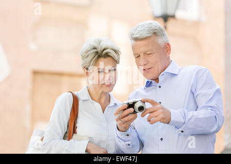 Smiling middle-aged couple reviewing photos on digital camera outdoors - Stock Photo