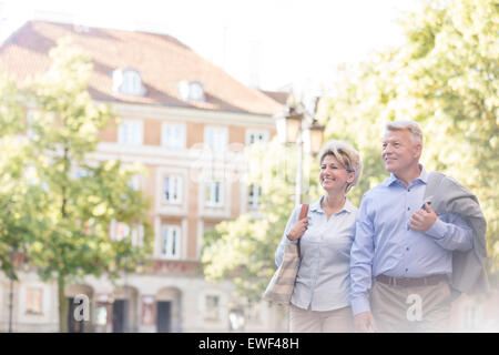 Happy middle-aged couple walking in city - Stock Photo