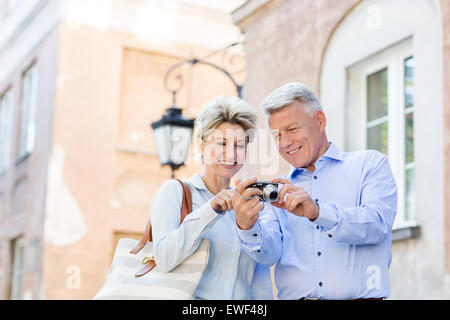 Happy middle-aged couple looking at pictures on digital camera in city - Stock Photo