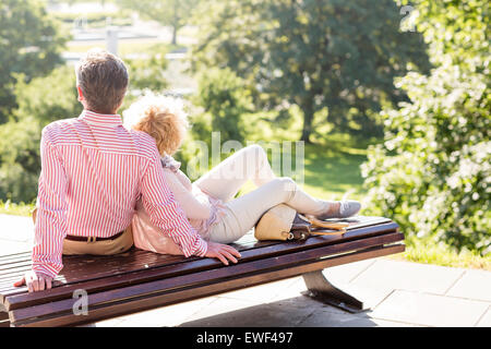 Middle-aged couple relaxing on park bench - Stock Photo