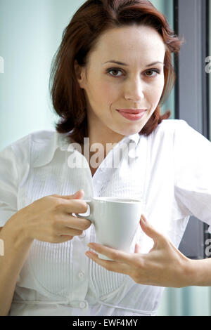 Young woman drinking coffee in the morning - Stock Photo
