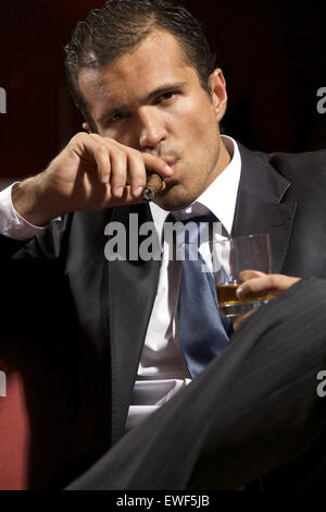 Portrait of young man smoking cigar and holding wineglass - Stock Photo