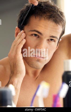Young man combing his hair - Stock Photo
