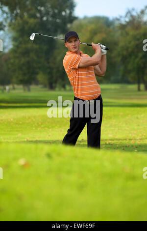 Young man swinging golf club - Stock Photo