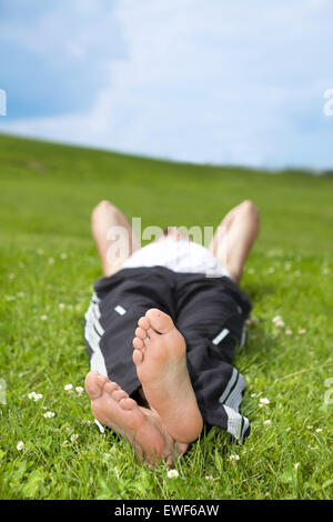 Young man lying on grass in park - Stock Photo