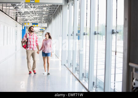 Full-length of couple walking in covered passage - Stock Photo