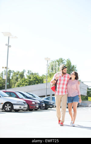 Affectionate couple walking on city street against clear sky - Stock Photo
