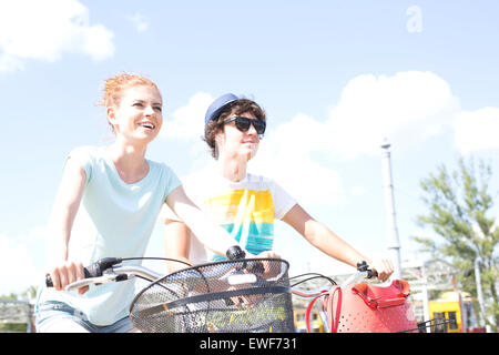 Smiling couple cycling against sky - Stock Photo