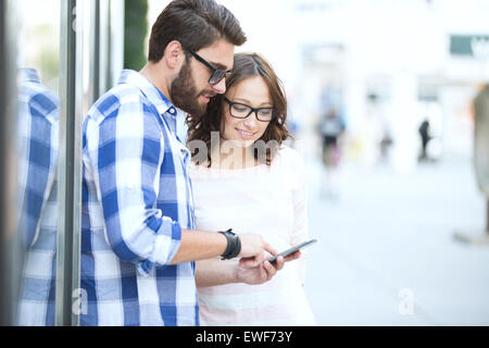 Smiling couple using smart phone together in city - Stock Photo