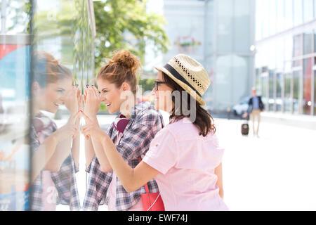 Happy female friends window shopping in city - Stock Photo