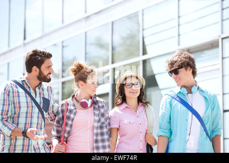 Male and female friends talking outside building - Stock Photo