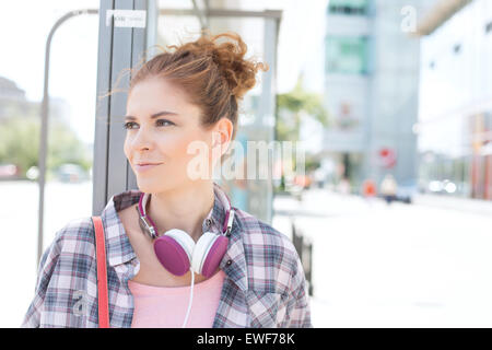 Smiling woman looking away while waiting at bus stop - Stock Photo