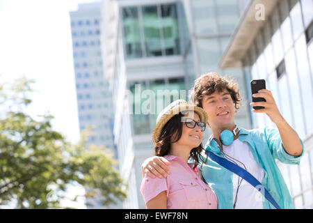 Smiling couple taking self portrait outside office building - Stock Photo