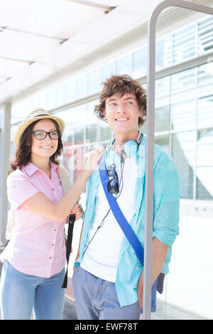 Smiling couple looking away while waiting at bus stop - Stock Photo