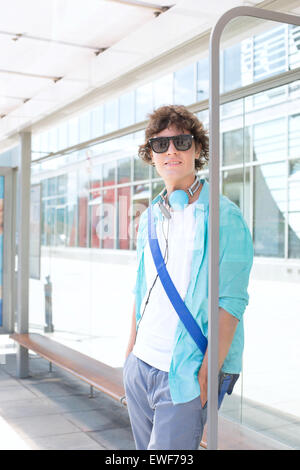 Portrait of confident man waiting at bus stop - Stock Photo