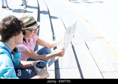 Happy couple reading map while sitting on steps outdoors - Stock Photo