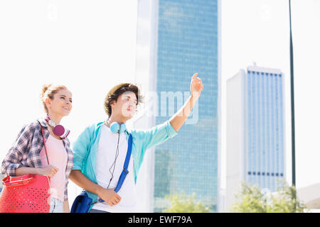 Happy woman standing with male friend hailing a taxi in city - Stock Photo