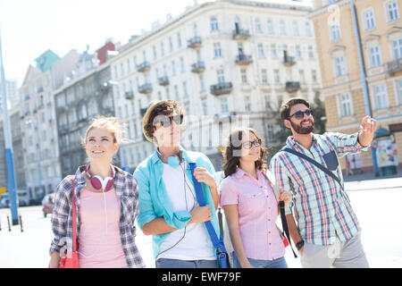 Happy man showing something to male and female friends on city street - Stock Photo