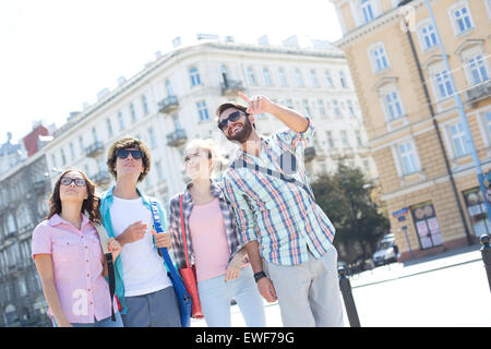 Smiling man showing something to friends on city street - Stock Photo