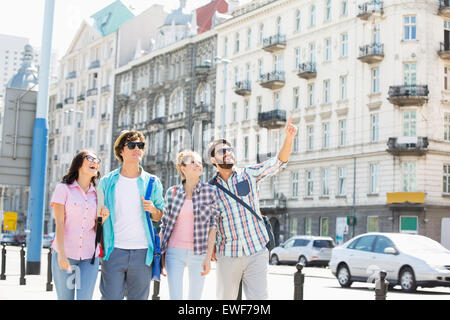 Happy man showing something to friends on city street - Stock Photo