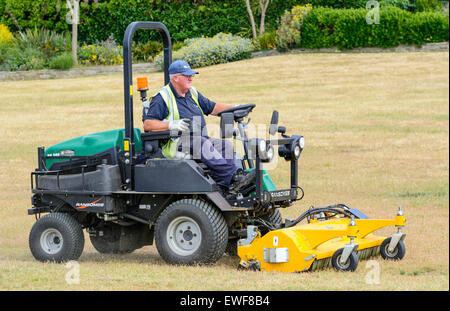 Old man riding on a Ransomes ride-on lawnmower while mowing and mulching the grass in a park. - Stock Photo