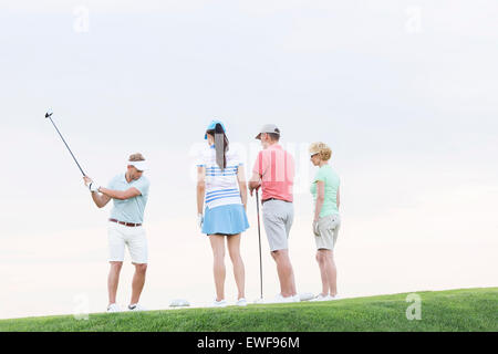 Group of friends looking at man playing golf against clear sky - Stock Photo