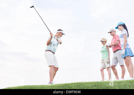Friends looking at man playing golf against sky - Stock Photo