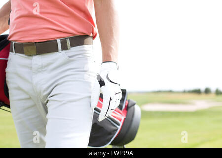 Midsection of man carrying golf club bag while walking at course - Stock Photo