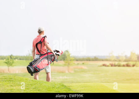 Rear view of man carrying golf club bag while walking at course - Stock Photo