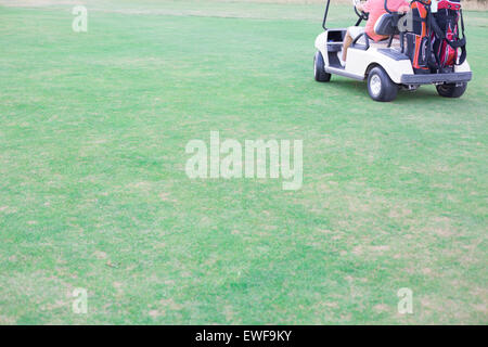 Low section of middle-aged man driving golf cart - Stock Photo