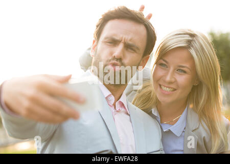 Playful business couple taking selfie outdoors on sunny day - Stock Photo