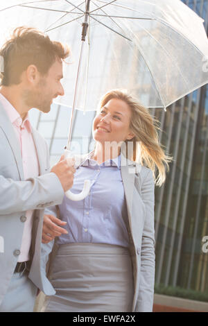 Happy business couple conversing under umbrella outdoors - Stock Photo