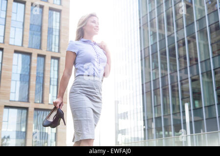 Low angle view of confident businesswoman holding high heels while standing outside office buildings - Stock Photo