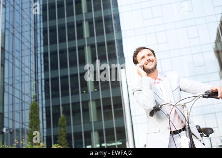 Low angle view of businessman answering mobile phone while sitting on bicycle outdoors - Stock Photo
