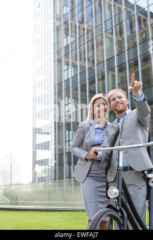 Happy businessman showing something to businesswoman in city - Stock Photo