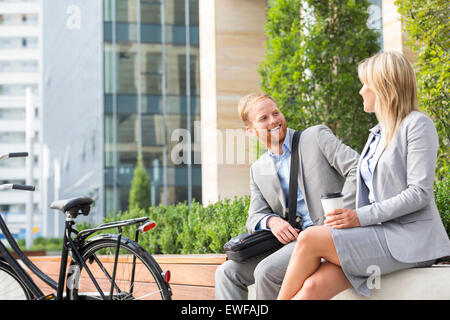Happy businessman talking to female colleague in city - Stock Photo
