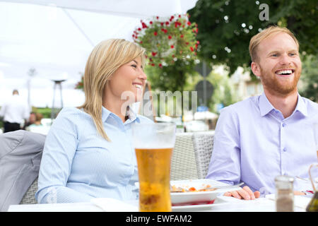 Happy businessman and businesswoman sitting at outdoor restaurant - Stock Photo