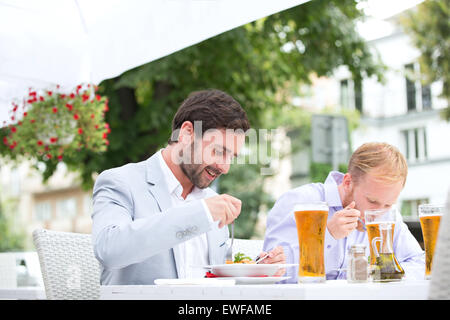 Businessmen eating food at outdoor restaurant - Stock Photo