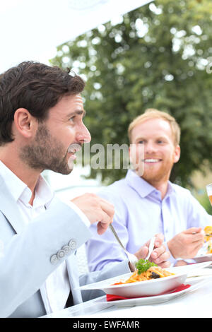 Businessmen having food at outdoor restaurant - Stock Photo