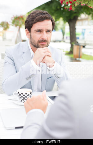Thoughtful businessman sitting with colleague at sidewalk cafe - Stock Photo