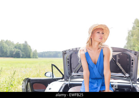 Woman looking away while sitting on convertible trunk against clear sky - Stock Photo