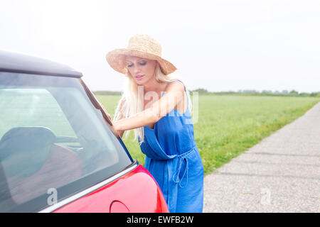 Woman pushing broken down car on country road against clear sky - Stock Photo