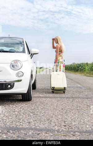 Woman looking at broken down car while pulling luggage on country road - Stock Photo