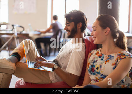 Casual business people using laptop in office - Stock Photo