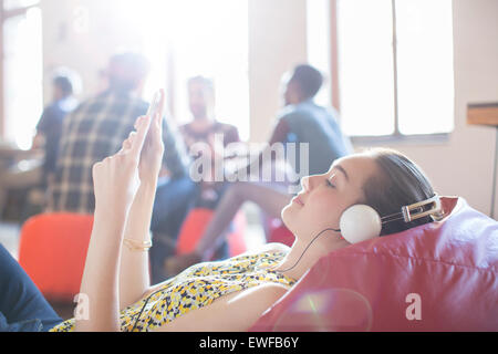 Casual businesswoman relaxing with headphones and digital tablet on bean bag chair - Stock Photo